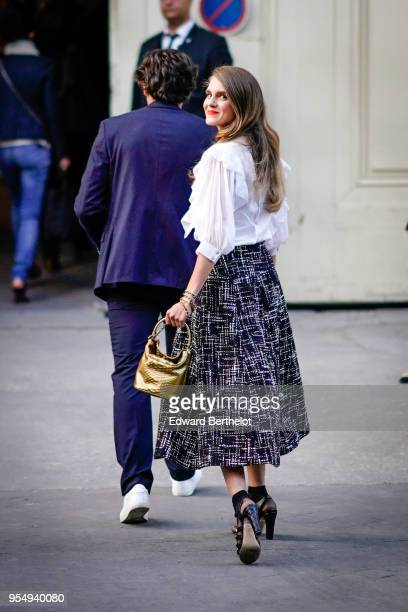 Dolores Doll wears a white ruffled shirt a golden Chanel bag a Chanel checked tweed skirt black shoes outside the Chanel Cruise 2018/2019 Collection...