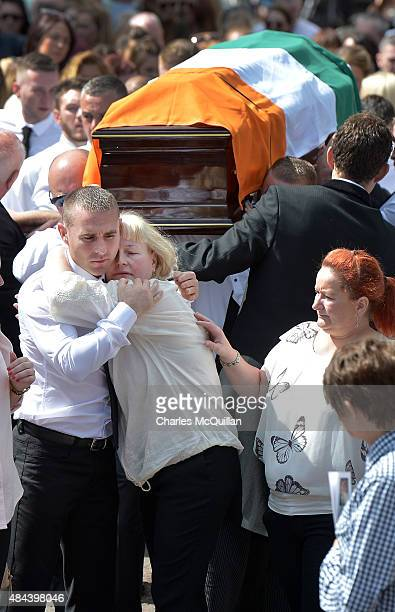 Dolores McGuigan wife to the murdered former IRA member Kevin McGuigan Sr is comforted as her husband's funeral takes place on August 18 2015 in...