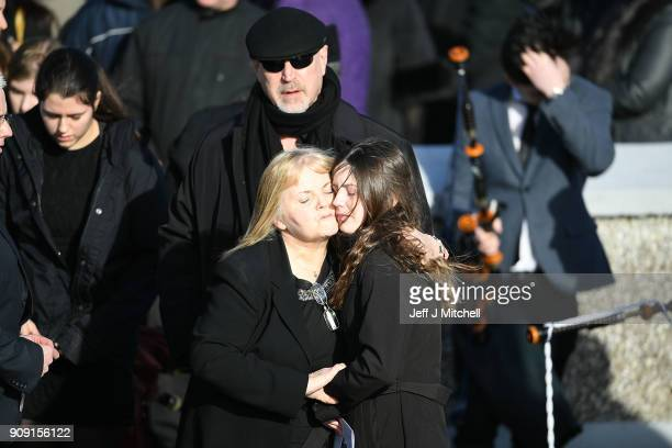 Dolores O'Riordan's exhusband Don Burton looks on as Dolores' mother Eileen O'Riordan receives an embrace as she attends the funeral of Dolores...