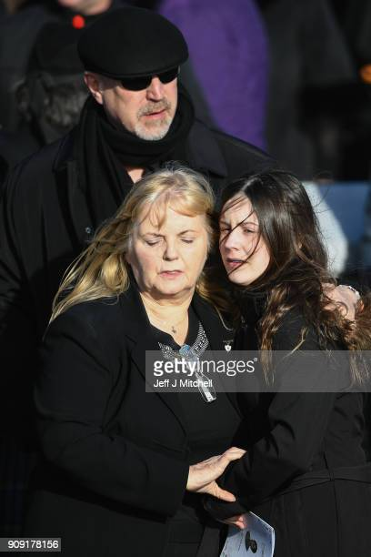 Dolores O'Riordan's exhusband Don Burton looks on as Dolores' mother Eileen O'Riordan receives an embrace from Molly O'Riordan as she attends the...