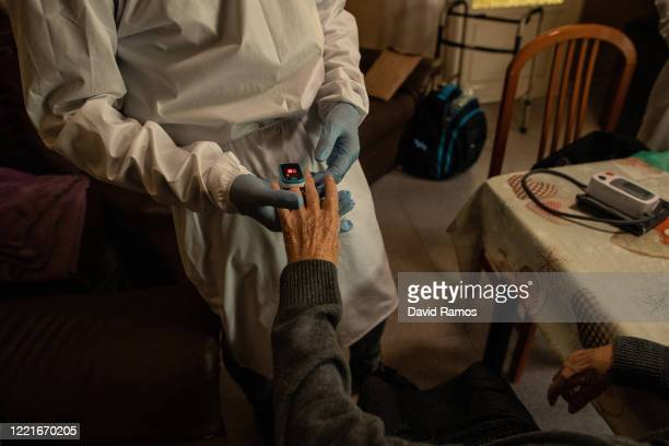 Dolores Solera has her oxygen level checked by an oximeter during a domiciliary visit on April 28, 2020 in Les Roquetes del Garraf, near Barcelona,...