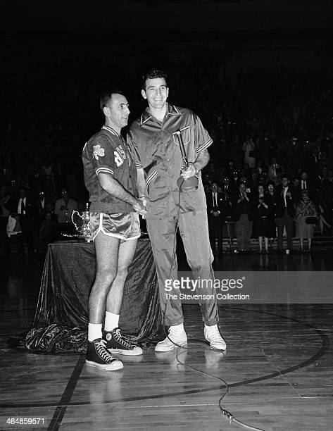 Dolph Schayes of the Syracuse Nationals presents Bob Cousy of the Boston Celtics with a sports achievement award for his outstanding performance as a...