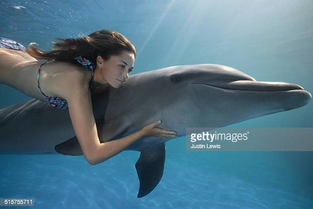 Dolphin with Young Woman Swimming Underwater