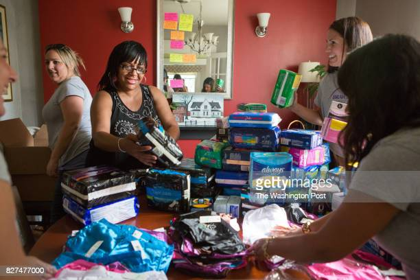 Dolphine Cooper in black tank top examines menstrual products as volunteers with the nonprofit BRAWS deliver underwear pads and tampons to women at...
