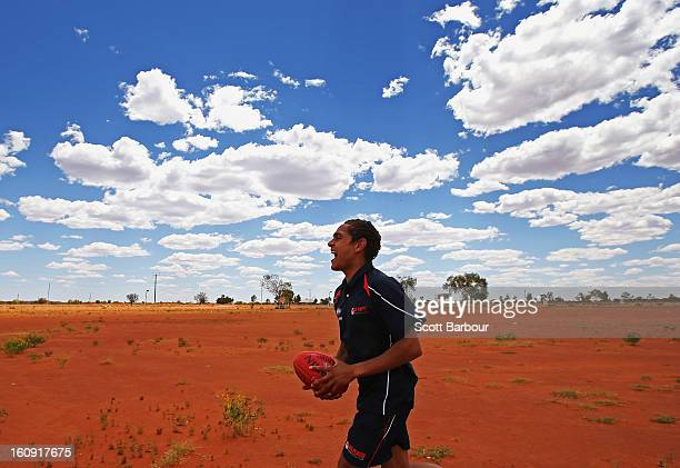 Dom Barry of the Indigenous All Stars runs with the ball on Yuendumu Football Oval as members of the Indigenous All Stars visit Yuendumu School in...