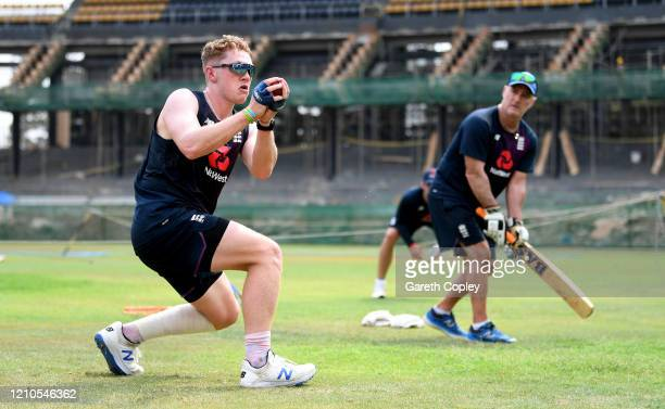 Dom Bess of England catches from the bat of batting coach Graham Thorpe during a nets session at Premadasa Cricket Stadium on March 05, 2020 in...