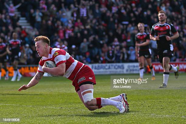 Dom Crosby of Wigan Warriors dives over the line to score his try during the Super League match between Wigan Warriors and St Helens at DW Stadium on...