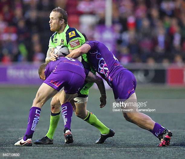 Dom Crosby of Wigan Warriors is tackled by Kevin Brown and Matt Whitley of Widnes Vikings during the First Utility Super League Round 19 match...