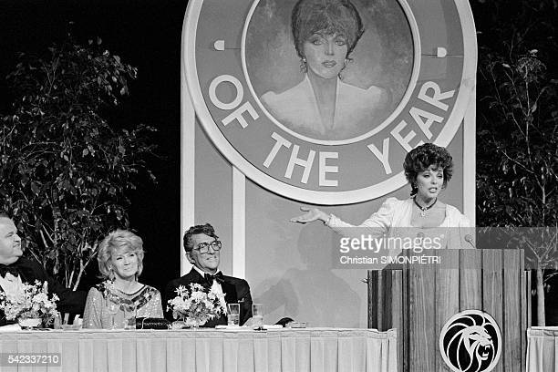 Dom DeLuise Angie Dickinson and Dean Martin join Joan Collins as she accepts Woman of The Year honors