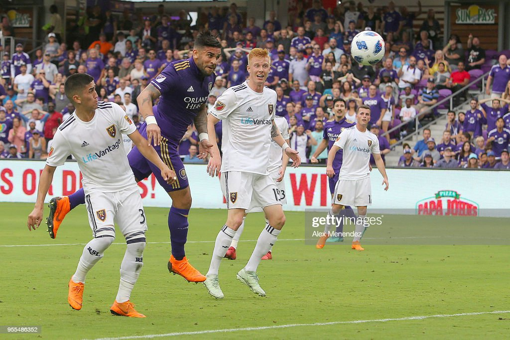 ORLANDO, FL - MAY 06 Dom Dwyer #14 of Orlando City SC heads the ball into the net past Adam Henley #3 of Real Salt Lake and Justen Glad #15 of Real Salt Lake during a MLS soccer match at Orlando City Stadium on May 6, 2018 in Orlando, Florida.