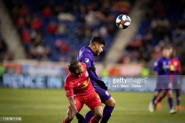 Dom Dwyer of Orlando City tries to head the ball against Kyle Duncan of New York Red Bulls during the MLS match between Orlando City SC and New York...