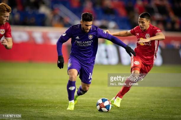 Dom Dwyer of Orlando City tries to maintain control against Sean Davis of New York Red Bulls during the MLS match between Orlando City SC and New...