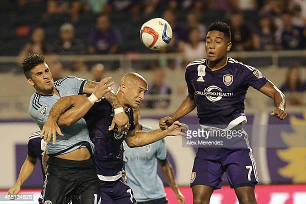 Dom Dwyer of Sporting Kansas City and Aurelien Collin of Orlando City SC fight for the ball in front of Cristian Higuita of Orlando City SC on a...