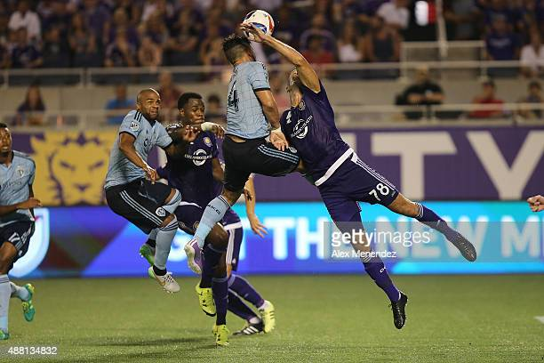 Dom Dwyer of Sporting Kansas City and Aurelien Collin of Orlando City SC fight for the ball on a corner kick during a MLS soccer match between...