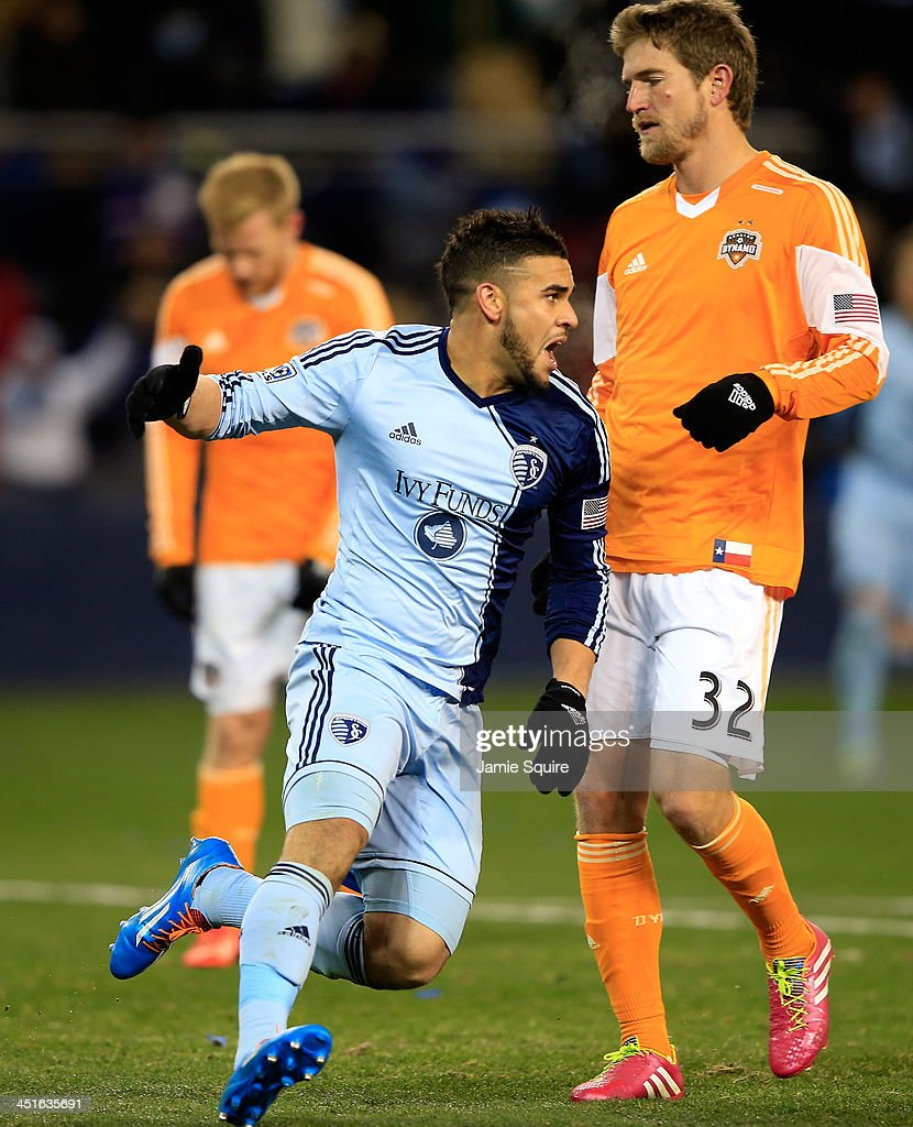Dom Dwyer #14 of the Sporting KC celebrates after scoring the game-winning goal as Bobby Boswell #32 of the Houston Dynamo looks down during Leg 2 of the Eastern Conference Championship at Sporting Park on November 23, 2013 in Kansas City, Kansas. Sporting KC defeated the Houston Dynamo with a final score of 2-1.