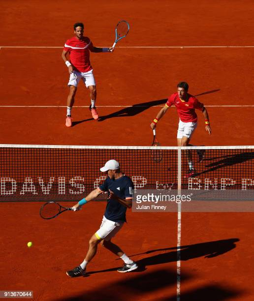 Dom Inglot tries to return as Jamie Murray of Great Britain take on Pablo Carreno Busta and Feliciano Lopez of Spain in the doubles during day two of...