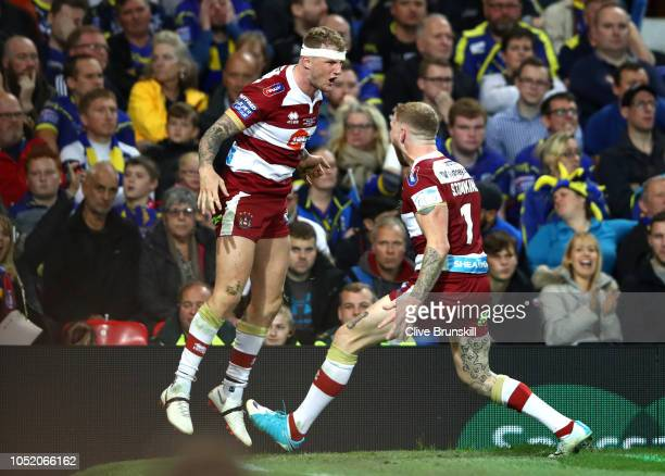 Dom Manfredi of Wigan Warriors celebrates with Sam Tomkins of Wigan Warriors after scoring his sides third try during the BetFred Super League Grand...