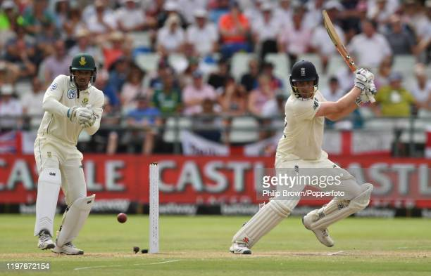 Dom Sibley of England hits a four as Quinton de Kock of South Africa looks on during Day Three of the Second Test between England and South Africa at...