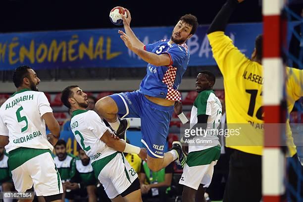 Domagoj Dunjak of Croatia is challenged by Hassan Aljanabi Mahdi Alsalem and Abdulazez Saeed of Saudi Arabia during the 25th IHF Men's World...