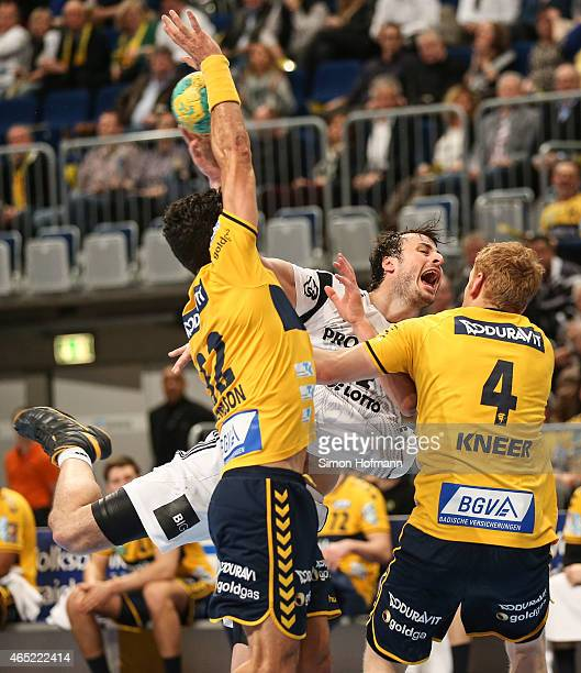 Domagoj Duvnjak of Kiel is challenged by Stefan Kneer and Alexander Petersson of RheinNeckar Loewen during the DHB cup quarter final match between...