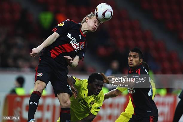 Domagoj Vida of Leverkusen jumps for a header with Wakaso Mubarak of Villarreal during the UEFA Europa League round of 16 first leg match between...