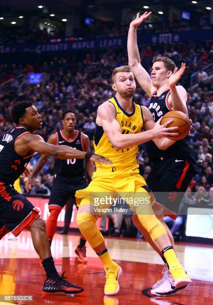 Domantas Sabonis of the Indiana Pacers dribbles the ball as Kyle Lowry and Jakob Poeltl of the Toronto Raptors defends during the first half of an...
