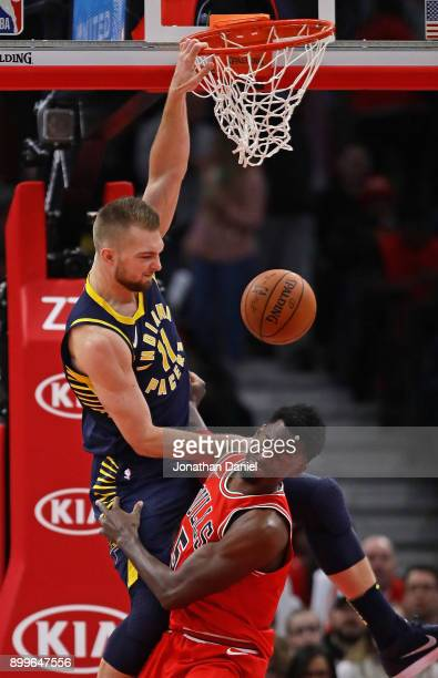 Domantas Sabonis of the Indiana Pacers dunks over Bobby Portis of the Chicago Bulls at the United Center on December 29 2017 in Chicago Illinois The...