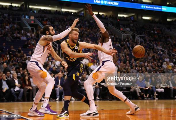 Domantas Sabonis of the Indiana Pacers passes the ball guarded by Ricky Rubio and Deandre Ayton of the Phoenix Suns during the first half of the NBA...