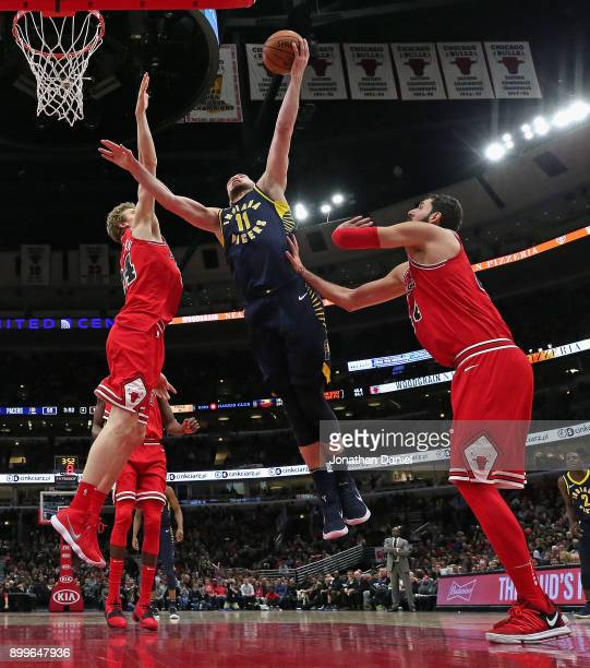 Domantas Sabonis of the Indiana Pacers puts up a shot between Lauri Markkanen and Nikola Mirotic of the Chicago Bulls at the United Center on...