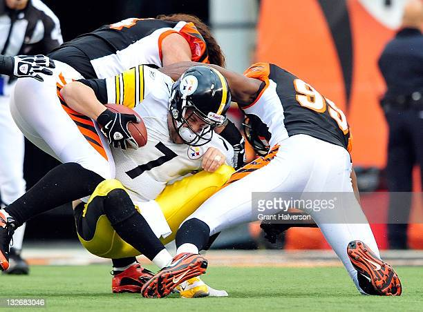 Domata Peko and Manny Lawson of the Cincinnati Bengals sacks quarterback Ben Roethlisberger of the Pittsburgh Steelers during play at Paul Brown...