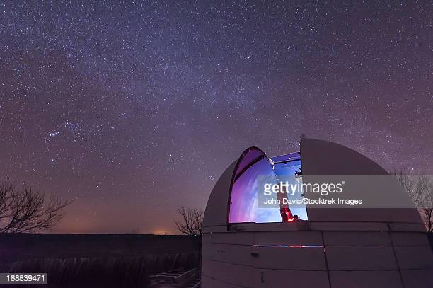 A domed observatory is open for business as a refractor telescope surveys the heavens, Crowell, Texas.