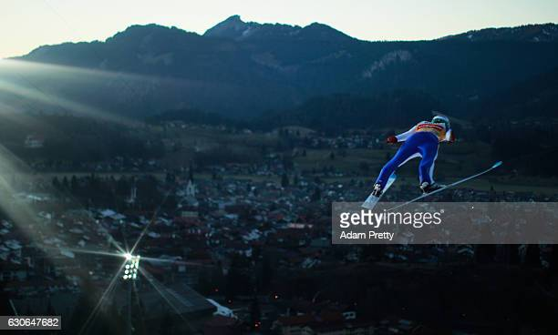 Domen Prevc of Slovenia soars through the air during his training jump on Day 1 of the 65th Four Hills Tournament ski jumping event on December 29...