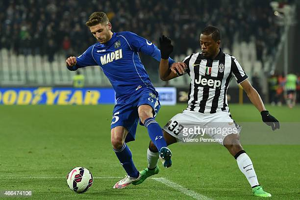 Domenico Berardi of US Sassuolo Calcio is challenged by Patrice Evra of Juventus FC during the Serie A match between Juventus FC and US Sassuolo...