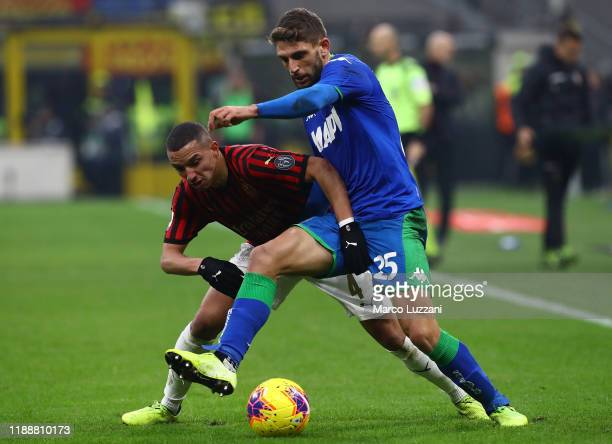 Domenico Berardi of US Sassuolo is challenged by Ismael Bennacer of AC Milan during the Serie A match between AC Milan and US Sassuolo at Stadio...