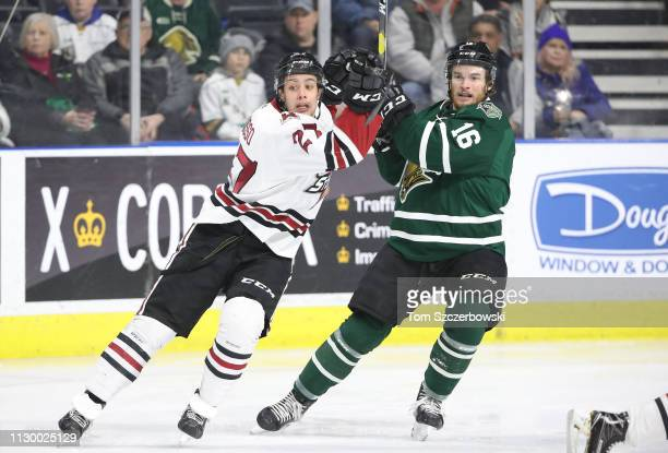 Domenico Commisso of the Guelph Storm and Kevin Hancock of the London Knights compete for positioning as they skate in the first period during OHL...