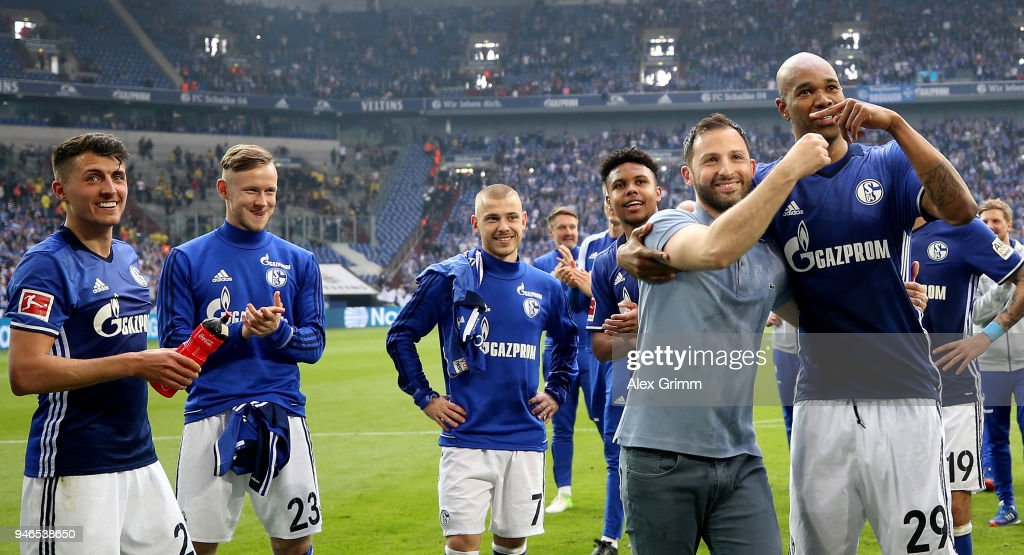 Domenico Tedesco (L), head coach of Schalke celebrate with Naldo after the Bundesliga match between FC Schalke 04 and Borussia Dortmund at Veltins-Arena on April 15, 2018 in Gelsenkirchen, Germany.
