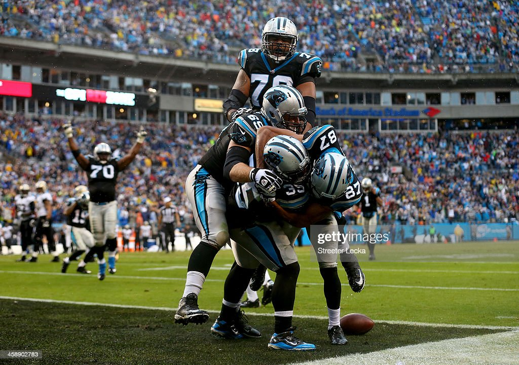 Domenik Hixon #87 of the Carolina Panthers makes the game winning touchdown in the fourth quarter to defeat the New Orleans Saints 17-13 as he celebrates with teammates Mike Tolbert #35, Jordan Gross #69 and Nate Chandler during their game at Bank of America Stadium on December 22, 2013 in Charlotte, North Carolina.