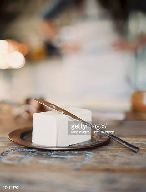 a domestic kitchen. a woman in the background. a slab of fresh organic butter, on a wooden dish. - mid section stock photos and pictures