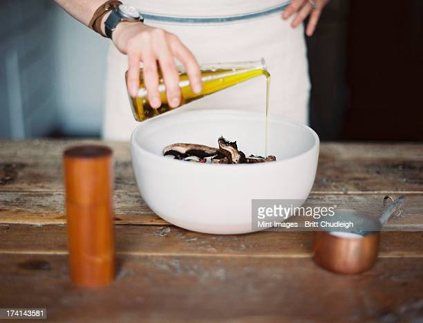 a domestic kitchen. a woman wearing an apron, dressing a fresh salad of vegetables in a bowl with oil.  - olive oil stock pictures, royalty-free photos & images