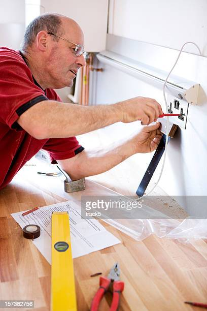 Domestic kitchen fitter installing an electrical wall plug socket