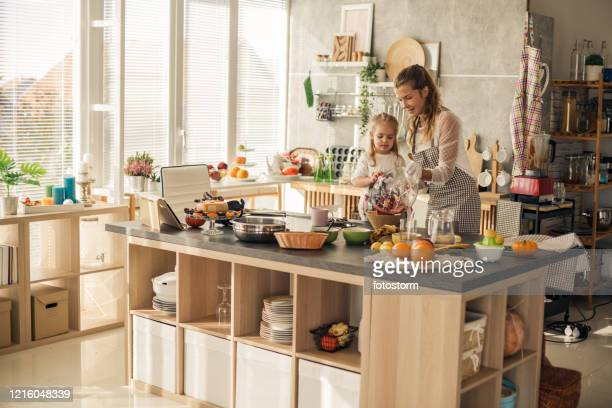 domestic kitchen of two generations cooking healthy vegan food - wide shot stock pictures, royalty-free photos & images