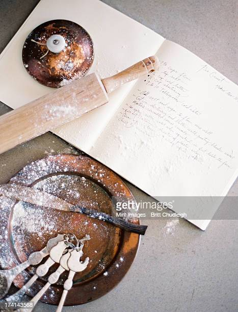 A domestic kitchen table. A large group of kitchen utensils, spoons, a pan and a board. Rolling pin. Flour and ingredients.
