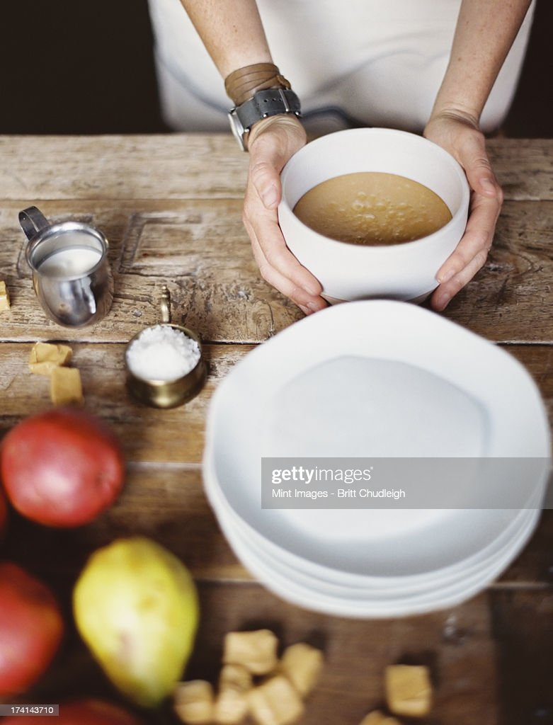 A domestic kitchen tabletop. A stack of white plates and fresh pears and a stack of sugar cubes. A bowl of  fudge sauce. : Stock Photo