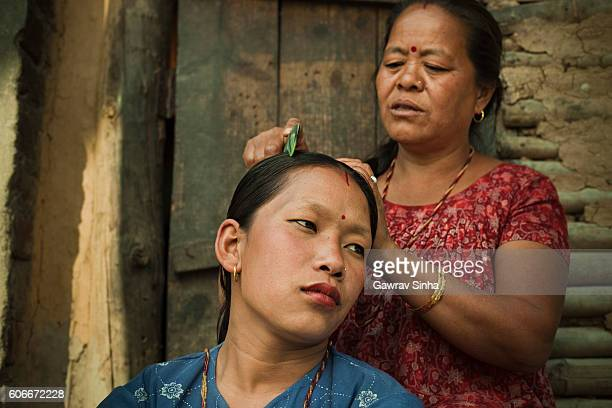 Domestic life of Asian peasant women, combing her daughter-in-law's hair.