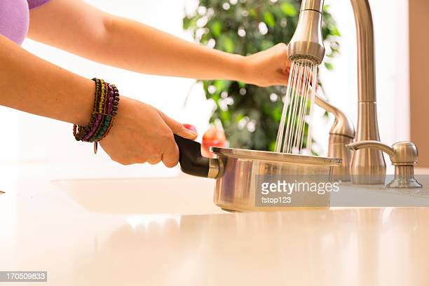 Domestic Life: Woman washing pot at the kitchen sink.