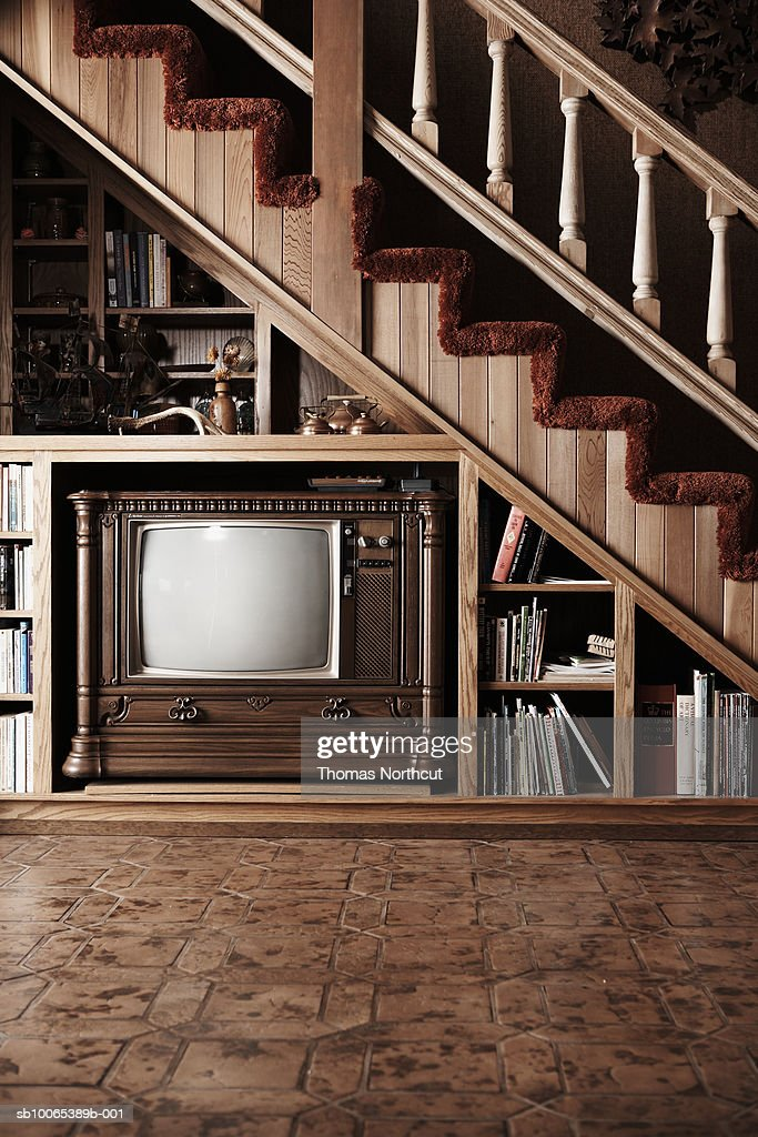 Domestic room with TV set under stairs : Stock Photo