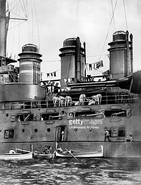 A domestic scene on a French battleship late 1910s Cows are eating on the deck and laundry is hung between the ship's funnels