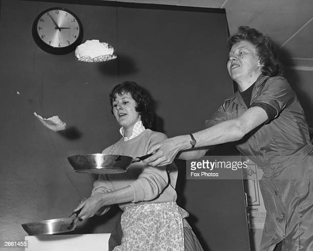 A domestic science teacher demonstrating the art of pancake tossing while one of her pupils practises behind her