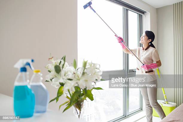 Domestic staff cleaning the window