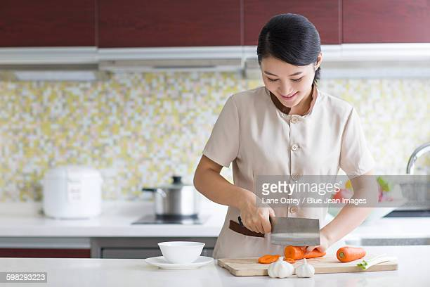 domestic staff cooking in kitchen - 根菜 ストックフォトと画像
